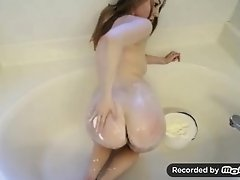 young busty girl plays with food in a bathroom