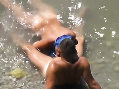 Girl sucks dick her boyfriend in the surf at a public beach