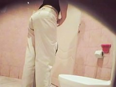 A woman wearing white jeans is pissing in the public toilet